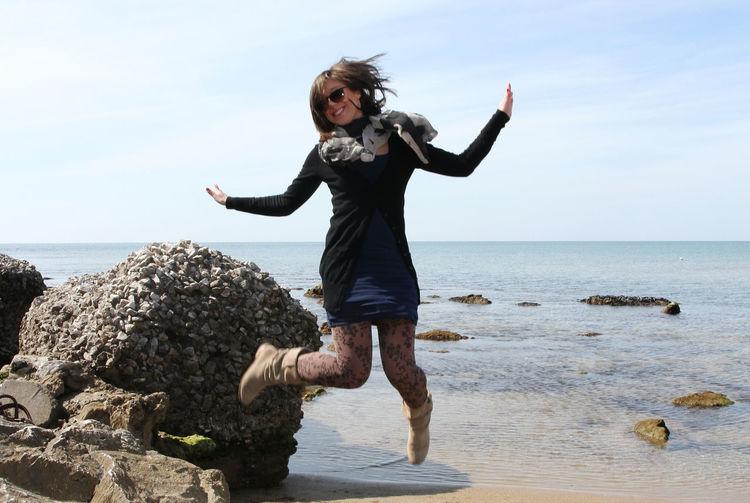Full length of woman jumping at beach against sky