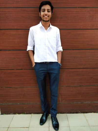 Portrait of young man standing against brick wall