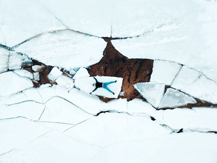 Directly above shot of man lying on ice formation