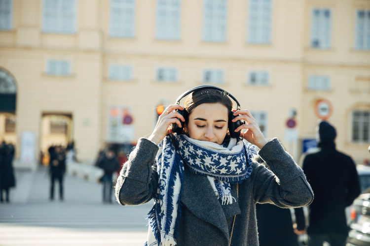 Young woman listening music on street in city
