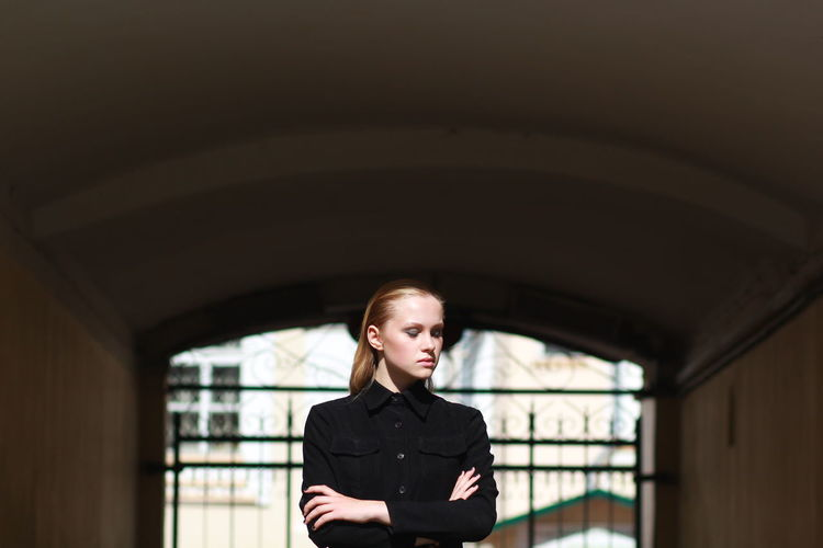 Young woman with arms crossed standing against gate