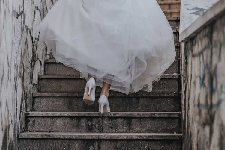 Low section of bride moving up on staircase