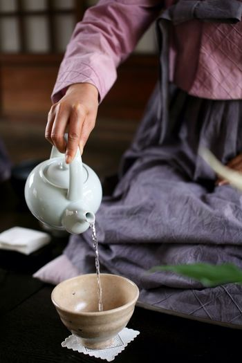 Close-up of hand serving tea