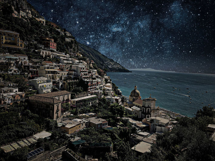 High angle view of townscape by sea against sky at night
