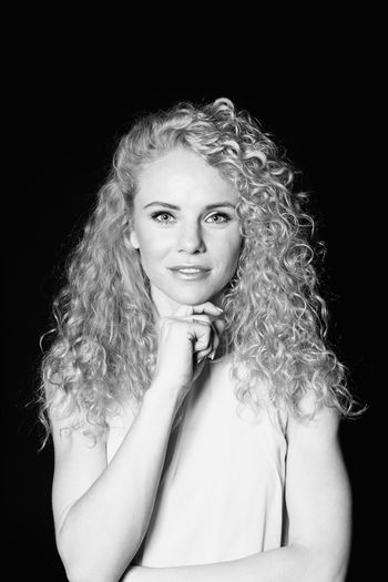 Portrait Of Woman With Curly Hair Against Black Background