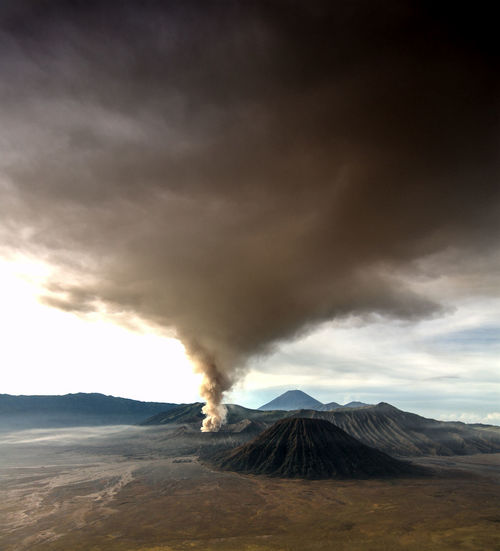 Smoke emitting from bromo volcanic mountain against sky