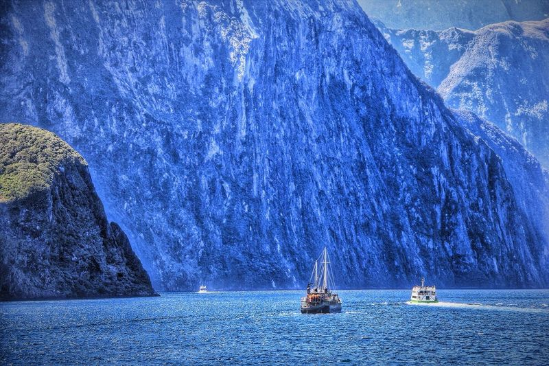 Boats in milford sound against mountains