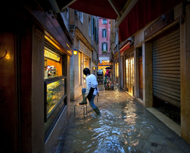 Rear view of sales clerk climbing on stool at water filled alley during flood