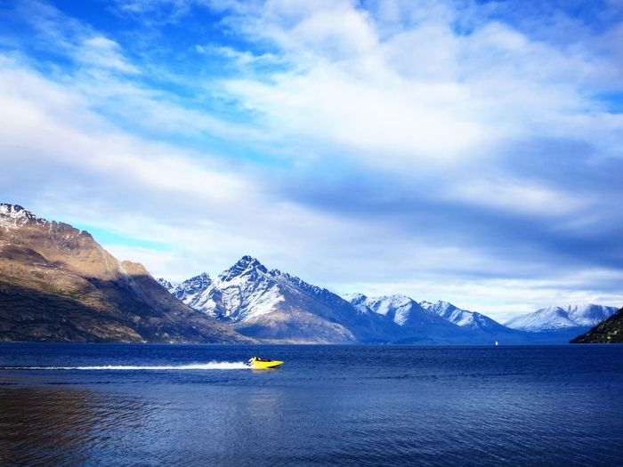 Mid distance speedboat on sea by mountain range against cloudy sky