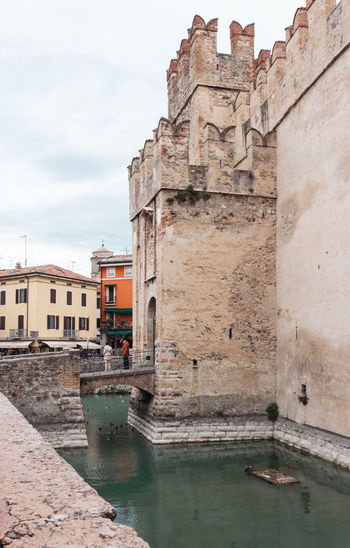 Sirmione, Italy - October 01, 2015 : Castello Scaligero fortress on Lake Garda. Tourists stand on the bridge leading to the fortress in Sirmione, Italy Architecture Building Castello Castle Day Destination Europe Famous Fortification Fortress Garda Italy Lago Lake Lombardy Medieval Old Outdoors Scaliger Sirmione Tourism Tower Travel Wall Water