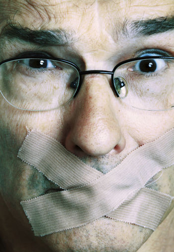Close-Up Portrait Of Man With Adhesive Bandage On Mouth