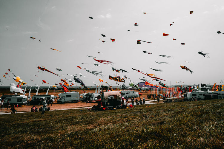 Low angle view of colorful kites flying over landscape against sky
