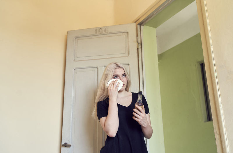 Woman standing against door at home