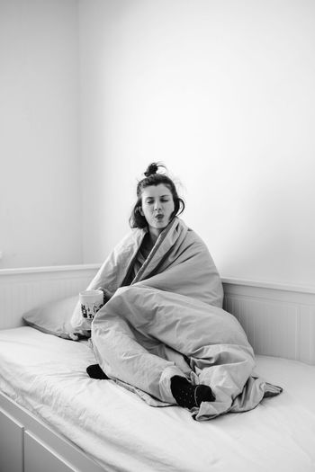Portrait of woman sitting on bed at home