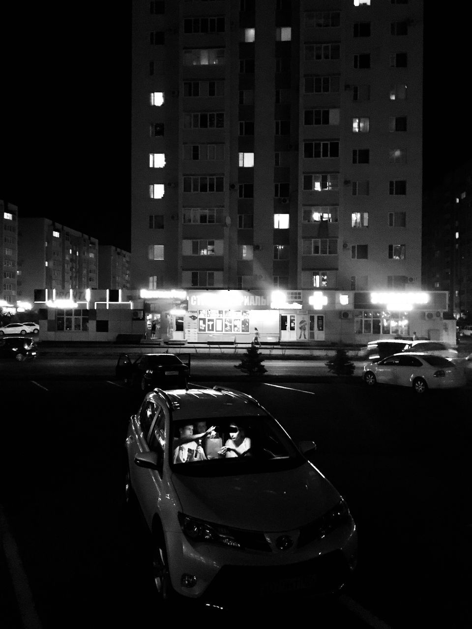 CARS ON CITY STREET BY ILLUMINATED BUILDINGS AT NIGHT