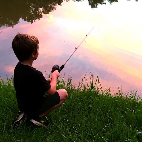 child fishing at the park Fishing Park Pond Nature Monroeville Alabama Sunset Child One Person Water Children Only People Sunset Sitting Outdoors Boys Nature Childhood