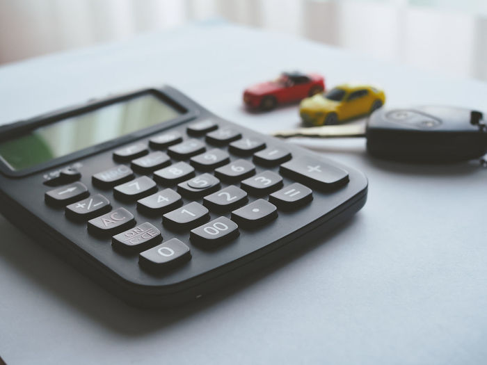 Accuracy Business Calculating Calculator Close-up Communication Finance Focus On Foreground High Angle View Indoors  Mathematics No People Number Red Selective Focus Still Life Table Technology Text Toy
