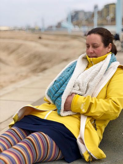 Woman In Warm Clothing Relaxing At Beach