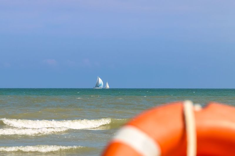Vew from shore to sailing boats far to the sea, Italy, Riccione Rimini Summer Italy. Riccione Emiliaromagna Riccione Italy Orange Color Lifebuoy Sea Horizon Over Water Water Nature Beauty In Nature Scenics Tranquil Scene Sky Day Nautical Vessel Outdoors Tranquility Beach No People Wave Sailing