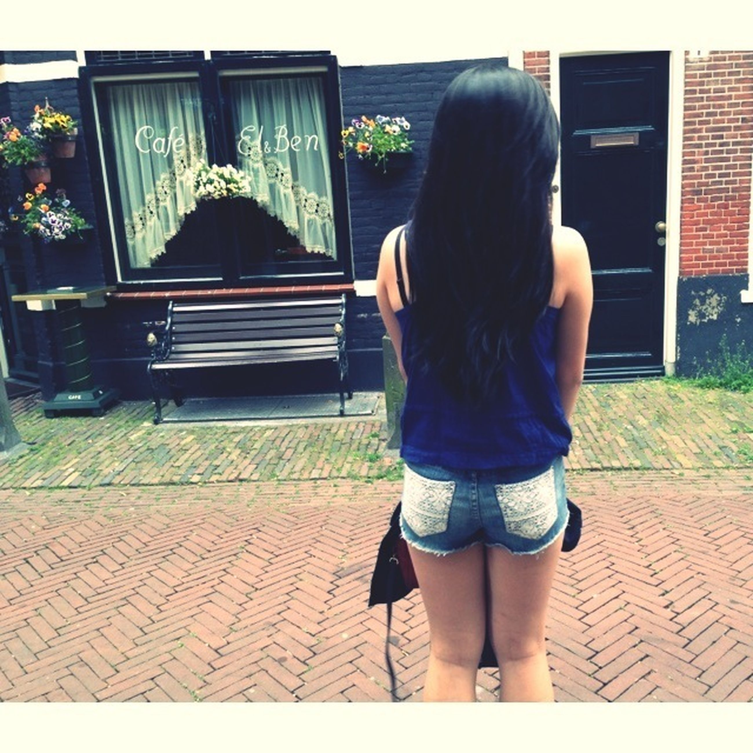 rear view, casual clothing, lifestyles, standing, full length, leisure activity, building exterior, built structure, architecture, sunlight, person, day, outdoors, three quarter length, childhood, sidewalk, side view, walking