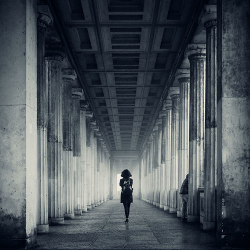 Rear view of woman walking on walkway amidst colonnades at alte nationalgalerie