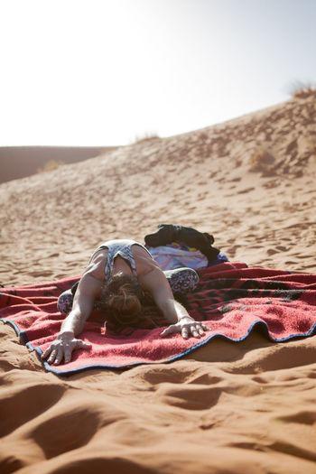 Woman Exercising In Desert Against Sky