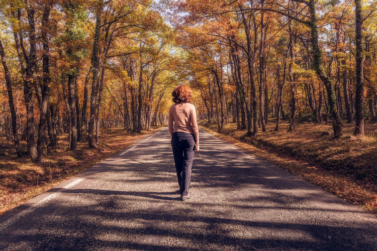 Rear view full length of woman standing on road amidst autumn trees