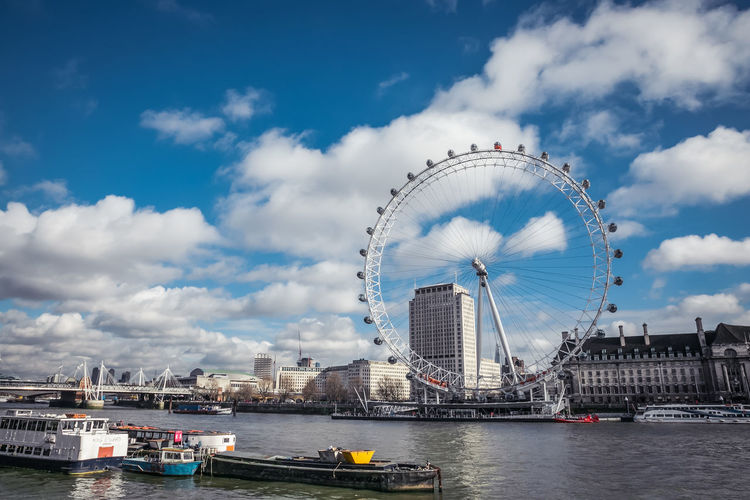 London Eye Ferris wheel across the river Thames. London Eye Ferris Wheel River Thames London United Kingdom England, UK Cloudscape River Water Panorama Famous Place No People Travel Destinations Amusement Park Ride Cityscape Outdoors Day Summer Cloud - Sky Long Shot Waterfront Tranquil Scene