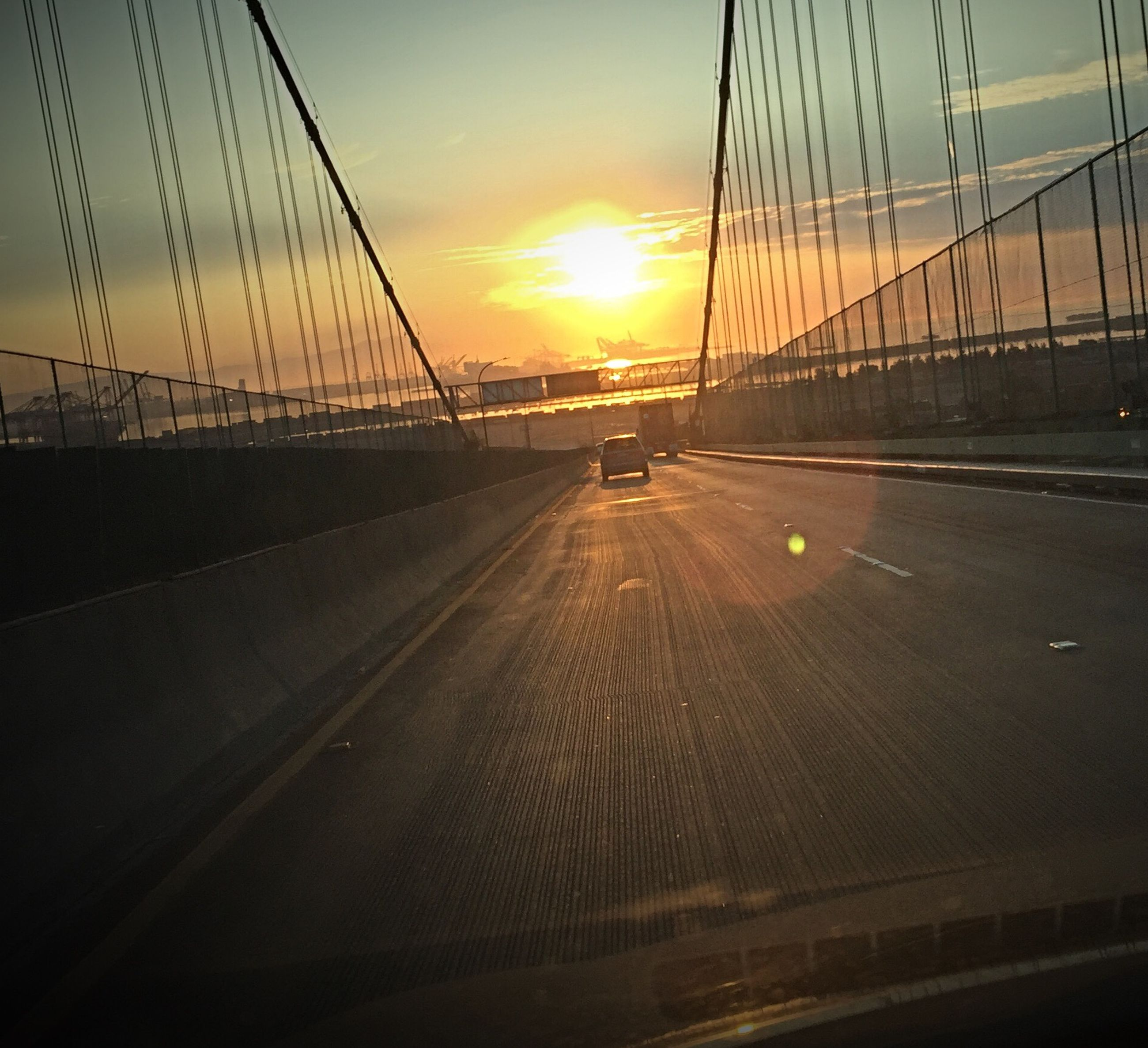 sunset, sun, orange color, transportation, connection, sky, silhouette, the way forward, sunlight, diminishing perspective, road, bridge - man made structure, scenics, built structure, sea, outdoors, beauty in nature, no people, nature, vanishing point