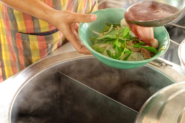 Midsection of man preparing food in bowl