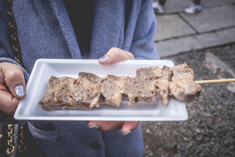 Midsection Of Woman Holding Meat In Plate While Standing At Footpath