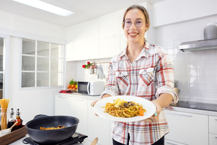 Portrait of smiling young woman having food at home
