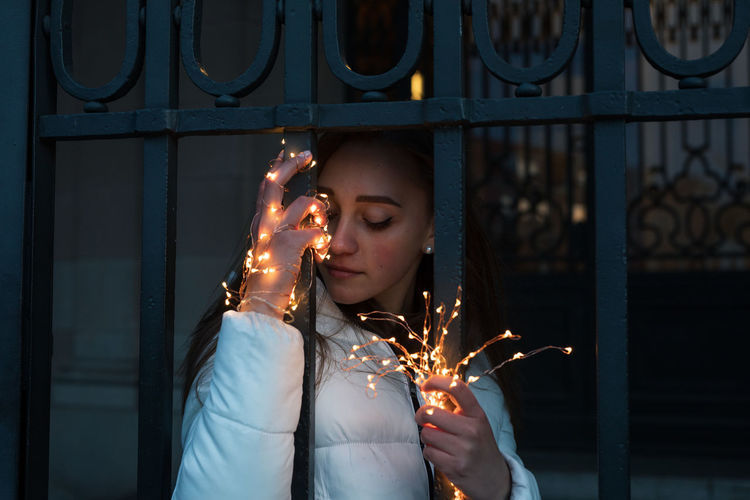 Young woman holding illuminated string light at night