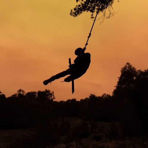 Silhouette man playing swing at sunset