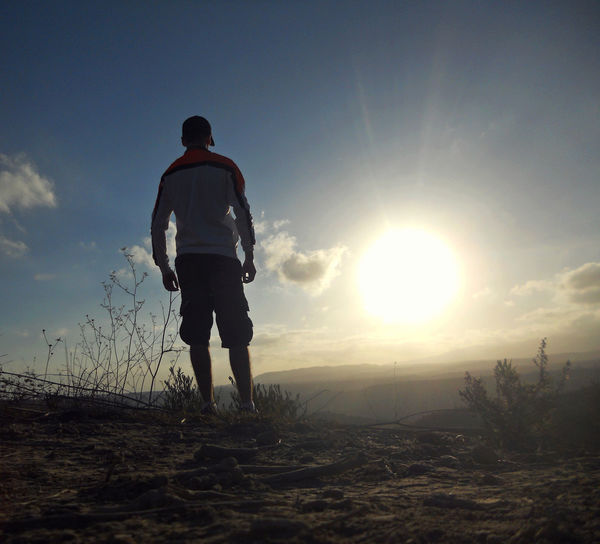 Rear View Of Man Standing On Field Against Sky During Sunset