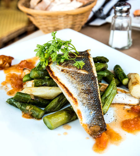 Close-up of fish with asparagus served on table