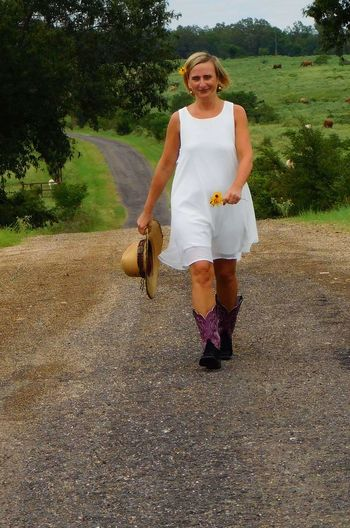 Walking uphill on country road One Person. One Woman Only Country Roads Country Life Countryside Tranquility One Young Woman Only Leisure Activity Only Women Adults Only Adult Mature Adult Agriculture People Front View Outdoors Rural Scene Summer Day Full Length Farmer Women Tree Nature Mammal