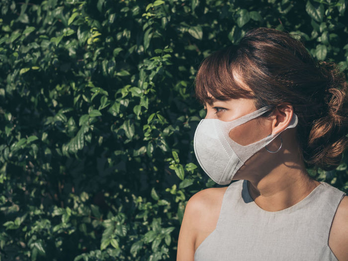 Woman wearing pollution mask while standing against plants
