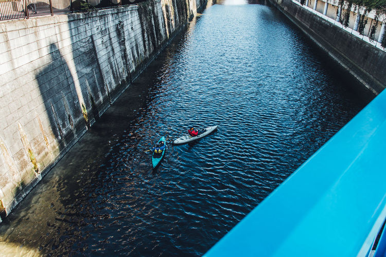 High Angle View Of People Canoeing In Canal