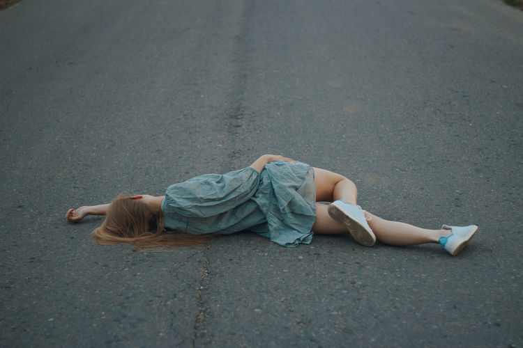 High angle view of woman lying on road