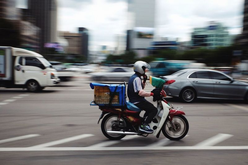 Man carrying container on motorcycle