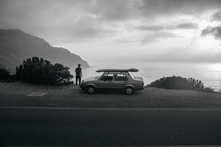 People on road by sea against sky