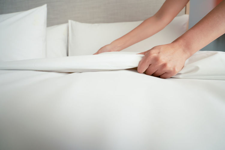 Female Hand set up white bed sheet in room hotel Bed Human Hand Indoors  One Person Hand Human Body Part Linen Real People Sheet Furniture White Color Lifestyles Women Textile Adult Leisure Activity Holding Home Interior Domestic Life Clean
