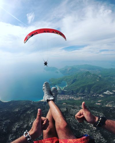 People paragliding over mountain against sky