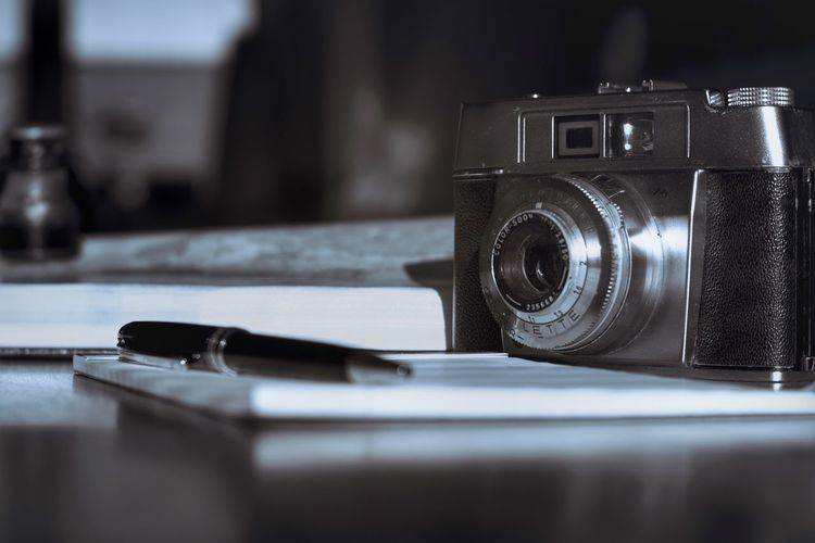 Close-up of camera on table in black and white