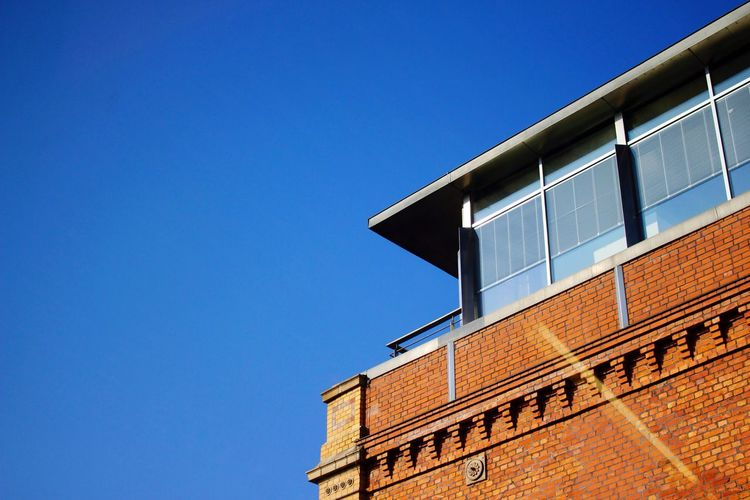 High section of cropped built structure against clear blue sky