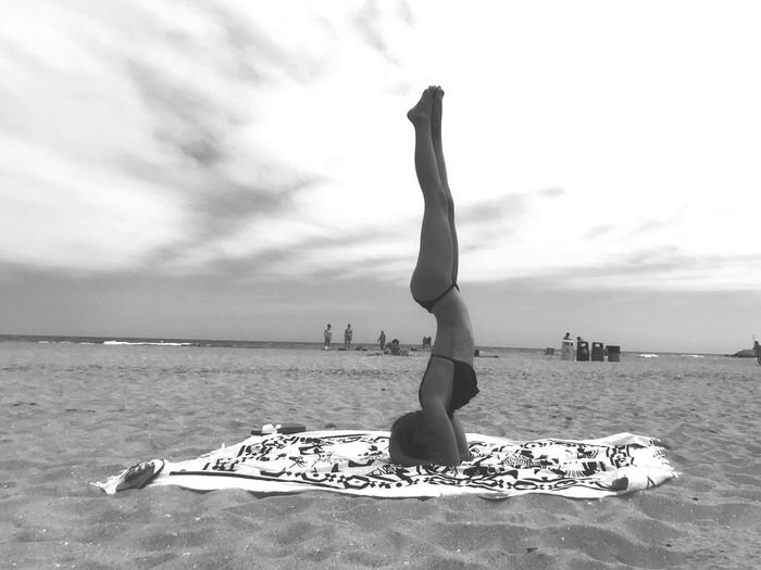Woman Doing Handstand At Beach Against Sky