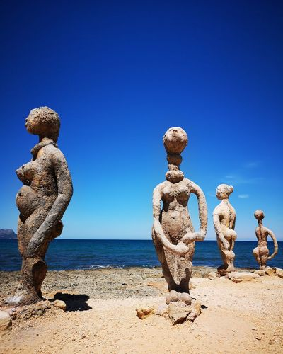 Statues at beach by sea against clear blue sky