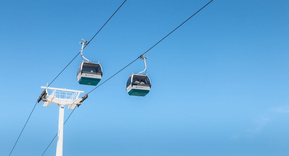 Low angle view of overhead cable car against blue sky