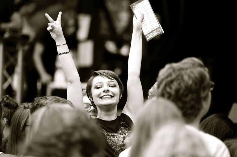 Portrait of young woman gesturing victory sign with arms raised